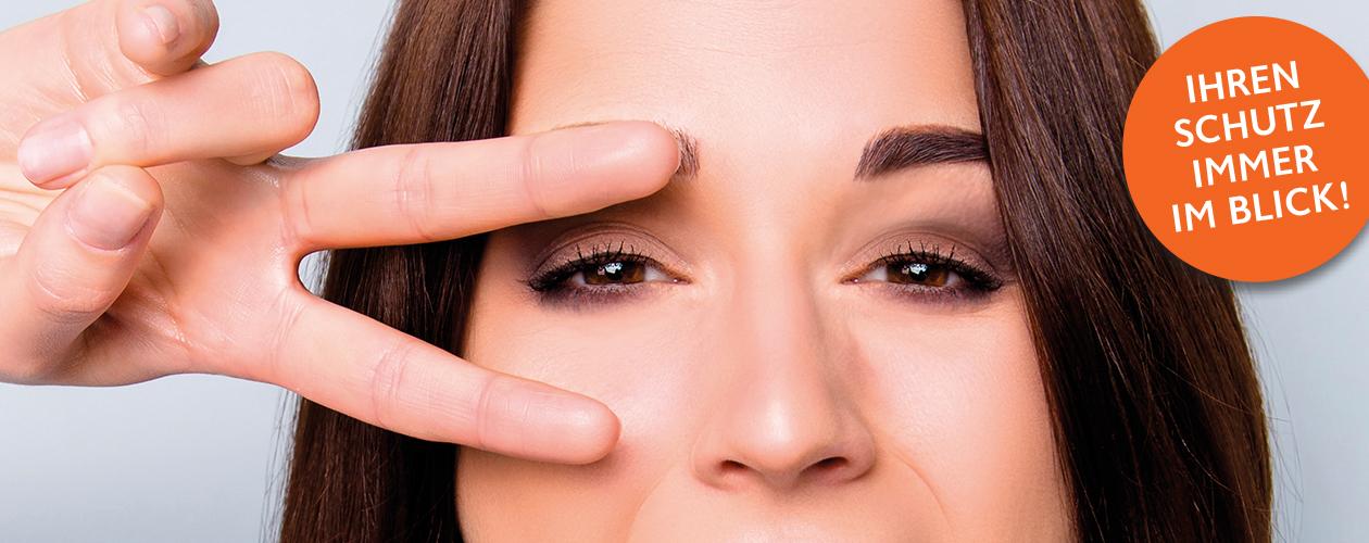 Versicherungslösungen für Leistungsträger - Gesicht von braunhaariger Frau, linkes Auge zwischen 2 Fingern für Peace Zeichen
