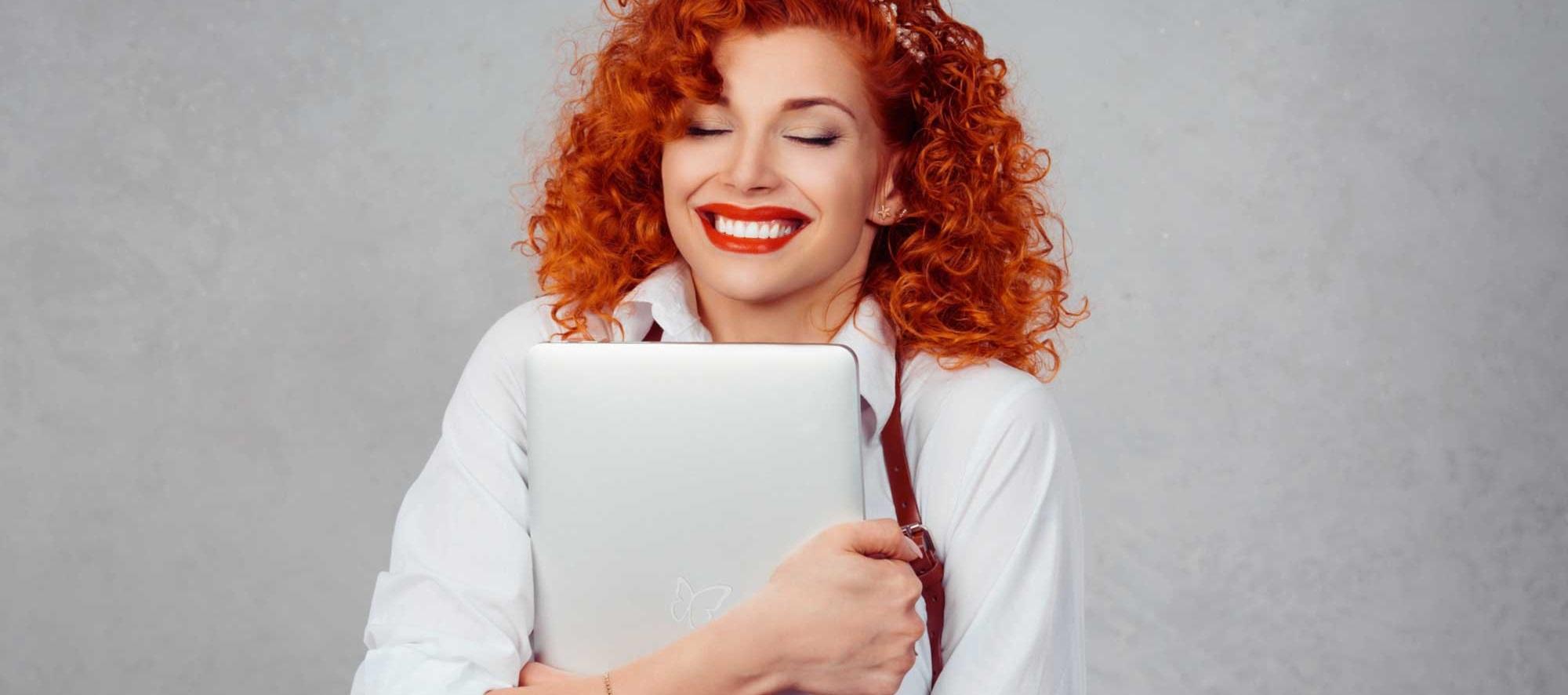 Schmetterling Marketinglösungen für Reisebüros - Bild von grinsender Frau mit roten, lockigen Haaren, die Laptop mit Schmetterling Logo umarmt