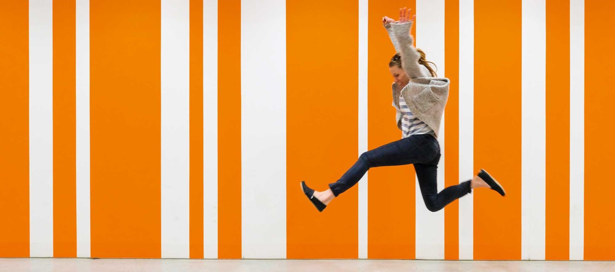 Schmetterling Startseite Partnerschaft - Frau hüpft freudig vor orange-weiß gestreiftem Hintergrund